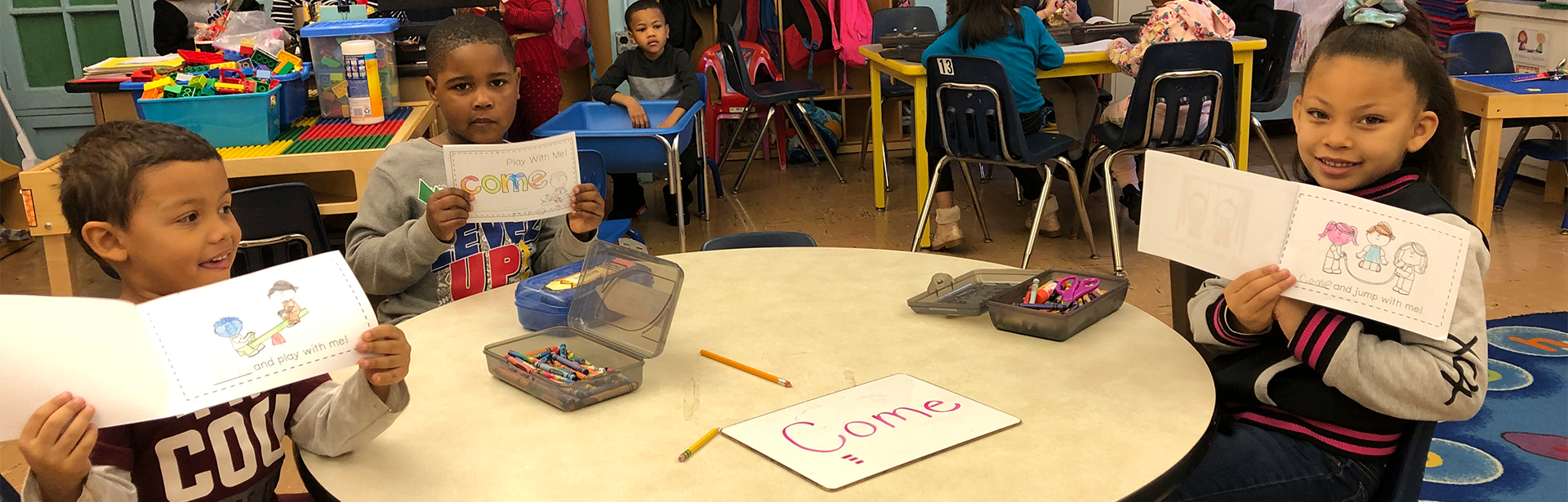 Students in class holding up art activity